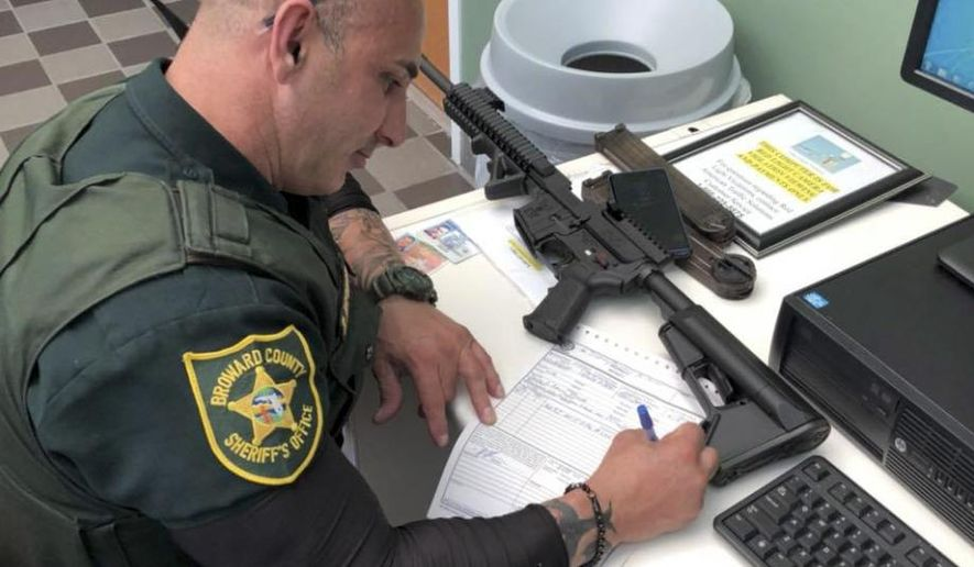 In this Feb. 16, 2018, photo provided by Ben Dickmann, a deputy at the Broward County sheriff's office in Ft. Lauderdale, Fla., processes paperwork to take possession of and destroy Dickmann's AR-style firearm. Dickmann decided to turn in his weapon after the shooting at Marjory Stoneman Douglas High School in nearby Parkland, Fla. (Ben Dickmann via AP)