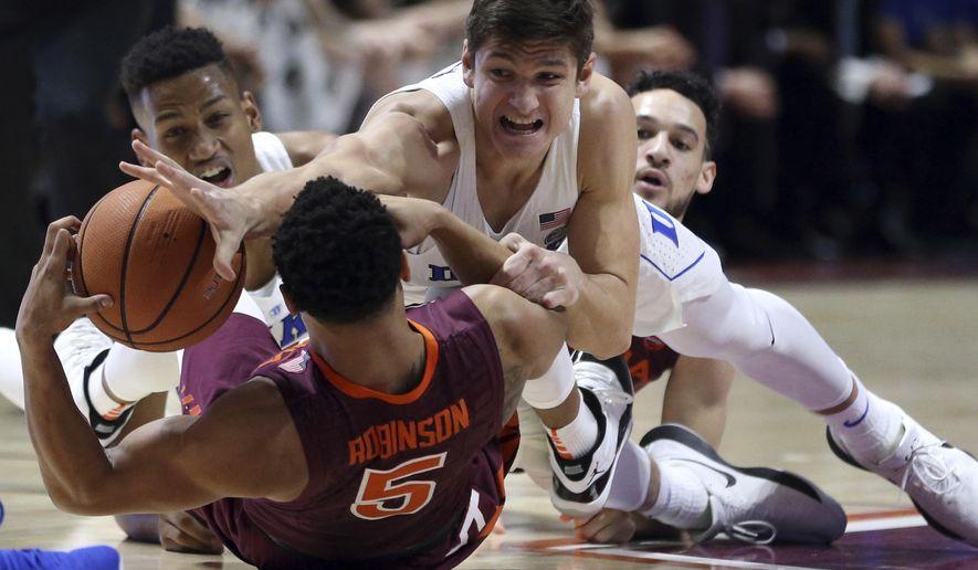 Duke's Grayson Allen (3) reaches for the ball on top of Virginia Tech's Justin Robinson (5) during the first half of an NCAA college basketball game Monday, Feb. 26, 2018, in Blacksburg, Va. (Matt Gentry/The Roanoke Times via AP)