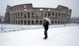 A man stands in front of the ancient Colosseum blanketed by the snow in Rome, Monday, Feb. 26, 2018. (AP Photo/Alessandra Tarantino)
