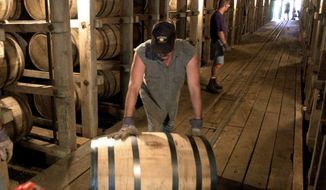 FILE - In this June 29, 2000, file photo, Tracy Matlock, left, and David Culpepper, right, move barrels of Jack Daniel's whiskey from one of the warehouses at the famous distillery in Lynchburg, Tenn. Jack Daniel's is turning to state lawmakers to ensure that distillers aren't subject to property tax on whiskey barrels in Tennessee, which the company says it hasn't had to pay since at least the end of Prohibition eight decades ago. (AP Photo/John Russell, File)