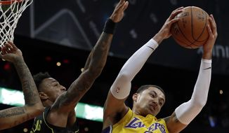 Los Angeles Lakers forward Kyle Kuzma (0) pulls down a rebound against Atlanta Hawks' John Collins during the first half of an NBA basketball game in Atlanta, Monday, Feb. 26, 2018. (AP Photo/John Bazemore