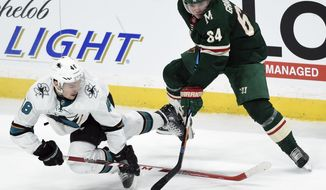 San Jose Sharks' Tomas Hertl (48) of the Czech Republic, falls as he vies for the puck against Minnesota Wild's Mikael Granlund (64), of Finland, during the overtime period of an NHL hockey game Sunday, Feb. 25, 2018, in St. Paul, Minn. The Wild won 3-2 in overtime. (AP Photo/Hannah Foslien)