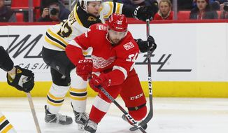 FILE - In this Feb. 6, 2018, file photo, Detroit Red Wings' Tomas Tatar (21) eludes Boston Bruins' Charlie McAvoy (73) in the second period of an NHL hockey game in Detroit. The expansion Vegas Golden Knightsv have added to their Western Conference-leading team by acquiring three-time 20-goal-scoring forward Tatar from Detroit. (AP Photo/Paul Sancya, File)