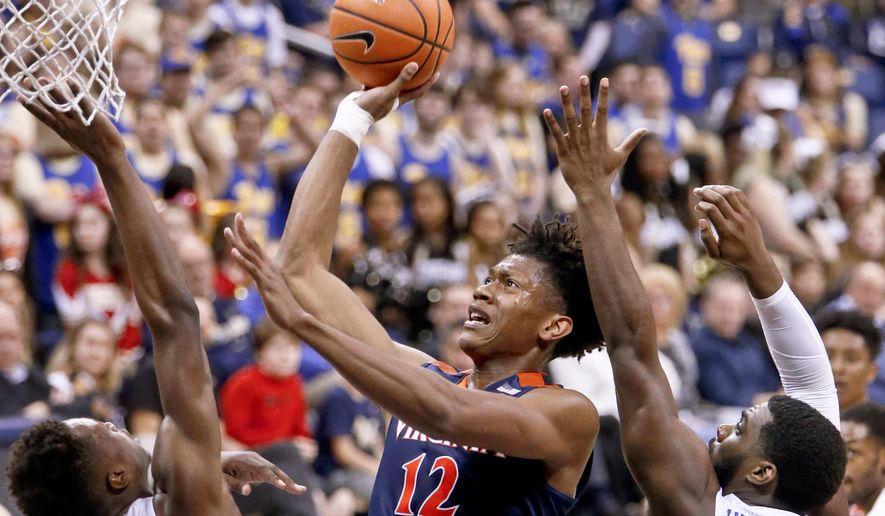 Virginia's De'Andre Hunter, center, shoots as Pittsburgh's Khameron Davis, left, and Jared Wilson-Frame, right, defends during the second half of an NCAA college basketball game, Saturday, Feb. 24, 2018, in Pittsburgh. Virginia won 66-37. (AP Photo/Keith Srakocic) ** FILE **