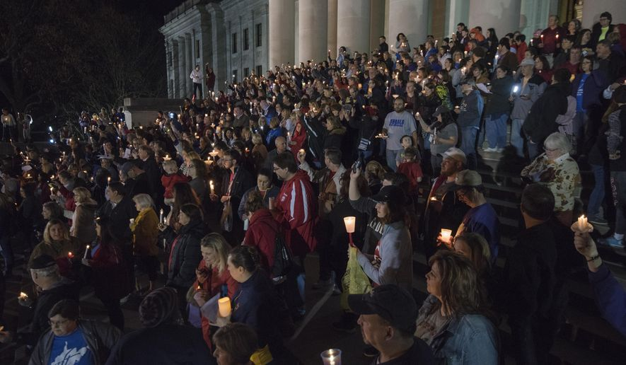 Hundreds attend a candlelight rally in support of the ongoing statewide teachers walkout outside of the capitol building in Charleston, W.V., on Sunday, Feb. 25, 2018. (Craig Hudson/Charleston Gazette-Mail via AP)