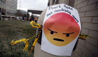 "A sign with an emoji reads ""Don't take net neutrality away"" is posted outside the Federal Communications Commission (FCC), in Washington, Thursday, Dec. 14, 2017, Thursday, Dec. 14, 2017. The FCC voted to eliminate net-neutrality protections for the internet. (AP Photo/Carolyn Kaster)"