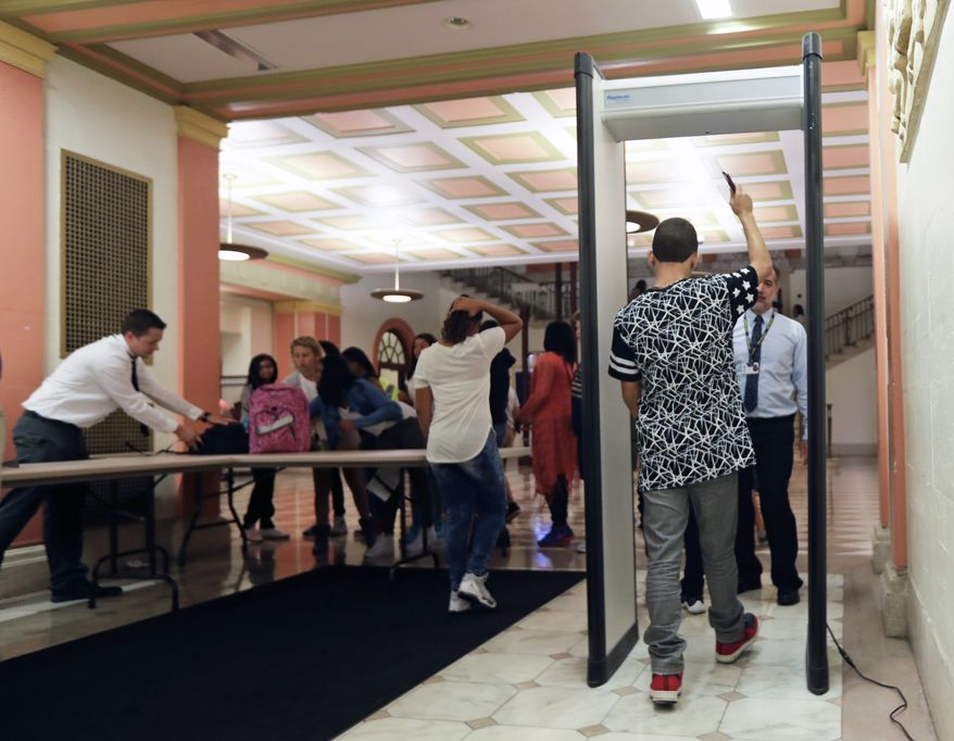 Students at William Hackett Middle School pass through metal detectors on the first day of school on Tuesday, Sept. 6, 2016, in Albany, N.Y. (AP Photo/Mike Groll)