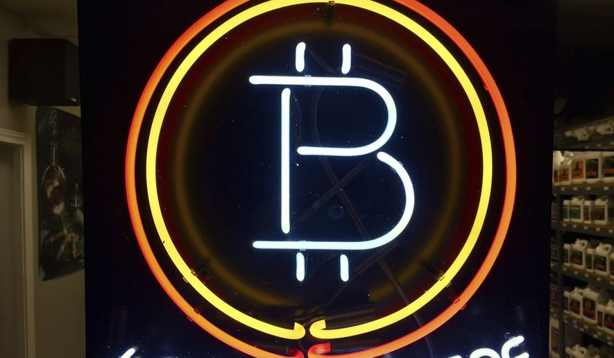 In this Feb. 7, 2018 file photo, a neon sign hanging in the window of Healthy Harvest Indoor Gardening in Hillsboro, Ore., shows that the business accepts bitcoin as payment. Purchases with bitcoin and other digital currencies remain rare relative to cash and credit cards. (AP Photo/Gillian Flaccus) **FILE**