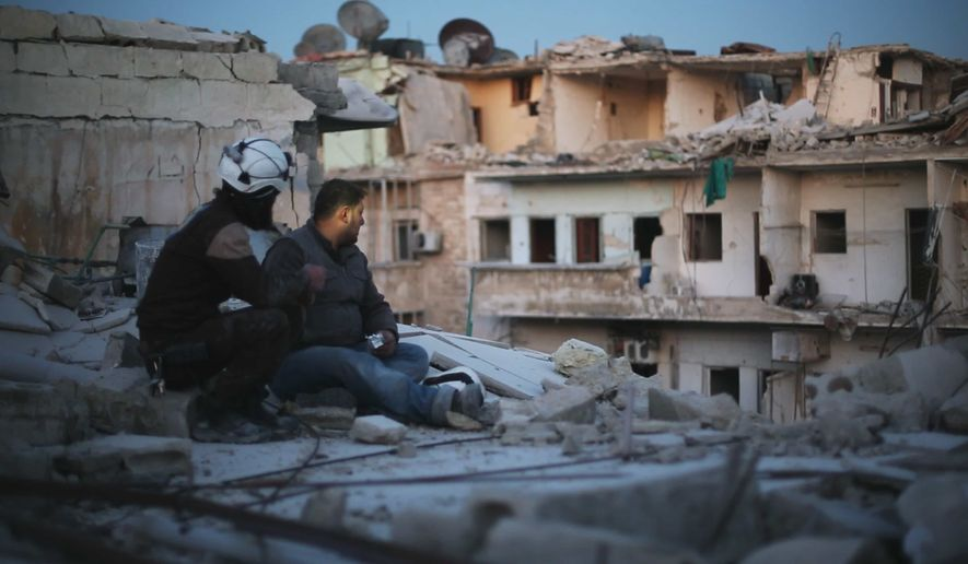 Members of Syria's 'White Helmet' civil defense force sit on top of a destroyed apartment block in eastern Aleppo, in a still from director Feras Fayyad's 'Last Men in Aleppo.' (Courtesy of Grasshopper Film.)