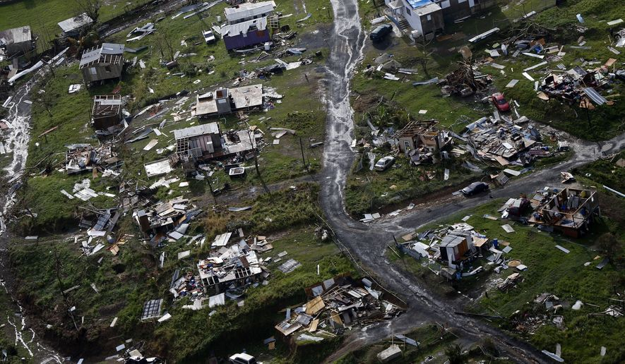 In this Sept. 28, 2017 file photo, destroyed communities are seen in the aftermath of Hurricane Maria in Toa Alta, Puerto Rico. Puerto Rico's governor is demanding action, on Tuesday, Feb. 27, 2018, from U.S. Congress after announcing that the Treasury Department has cut a nearly $5 billion disaster relief loan by more than half. (AP Photo/Gerald Herbert, File)
