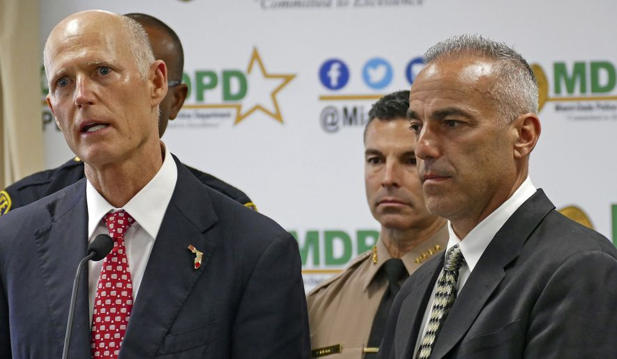 Florida Gov. Rick Scott talks alongside Andrew Pollack, right, whose daughter Meadow was fatally shot in Parkland during press conference at Miami-Dade Police Department in Doral on Tuesday, Feb. 27, 2018. Scott will highlight his action plan to make major changes to help keep Florida students safe, including a $500 million investment in school safety and mental health. (C.M. Guerrero/Miami Herald via AP)