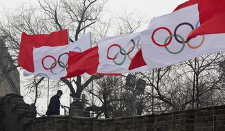 A security person stands near the Olympic flags during a ceremony to mark the arrival of the Olympic flag and start of the flag tour for the Winter Olympic Games Beijing 2022 at a section of the Great Wall of China in Beijing Tuesday, Feb. 27, 2018. (AP Photo/Ng Han Guan)