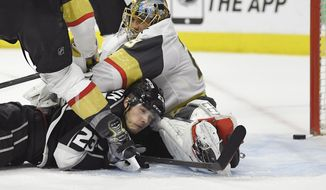 Los Angeles Kings right wing Dustin Brown, left, lays on the ice after scoring the game-winning goal past Vegas Golden Knights goaltender Marc-Andre Fleury during the overtime period of an NHL hockey game, Monday, Feb. 26, 2018, in Los Angeles. The Kings won 3-2. (AP Photo/Mark J. Terrill)