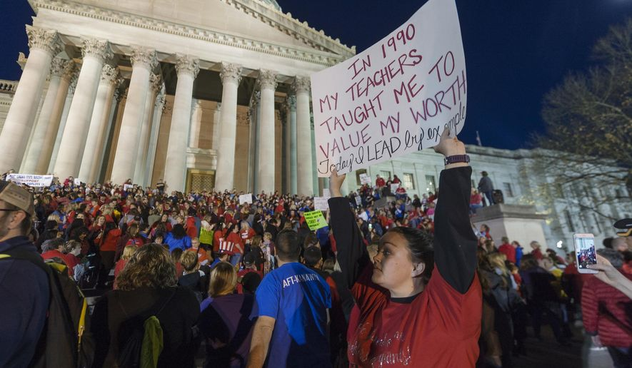 Jennyerin Steele Staats, a special education teacher from Jackson County holds her sign aloft outside of the capitol building after WVEA President Dale Lee outlined the terms for ending the walkout on the fourth day of statewide walkouts in Charleston, W.Va., Tuesday, Feb. 27, 2018. Striking teachers are to return to the classroom on Thursday, Justice said in announcing he is offering teachers and school service personnel a revised 5 percent pay raise in the first year to end their statewide walkout. (Craig Hudson/Charleston Gazette-Mail via AP)