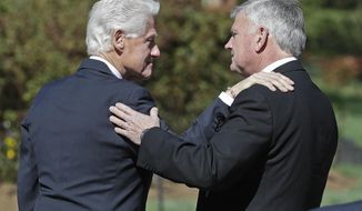 Former President Bill Clinton, left, greets Franklin Graham as he arrives to pay respects to Rev. Billy Graham during a public viewing at the Billy Graham Library in Charlotte, N.C., Tuesday, Feb. 27, 2018. (AP Photo/Chuck Burton)