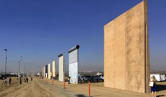 FILE - This Oct. 26, 2017 file photo shows prototypes of border walls in San Diego. A federal judge in San Diego who was taunted by Donald Trump during the presidential campaign has sided with the president on a challenge to building a border wall with Mexico. U.S. District Judge Gonzalo Curiel on Tuesday, Feb. 27, 2018 rejected arguments by the state of California and advocacy groups that the administration overreached by waiving laws requiring environmental and other reviews before construction could begin. (AP Photo/Elliott Spagat, File)