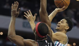 Charlotte Hornets' Jeremy Lamb, right, gets his shot off over Chicago Bulls' Noah Vonleh, left, during the first half of an NBA basketball game in Charlotte, N.C., Tuesday, Feb. 27, 2018. (AP Photo/Bob Leverone)