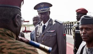 FILE - In this Wednesday Sept. 23, 2015 file photo, Burkina Faso coup leader Gen. Gilbert Diendere, center, greets people at the airport during the arrival of Niger's President Mahamadou Issoufou for talks in Ouagadougou, Burkina Faso. The trial for 84 people accused of masterminding a 2015 coup attempt in Burkina Faso began Monday Feb.26, 2018 in the West African nation's capital amid tight security. (AP Photo, file)