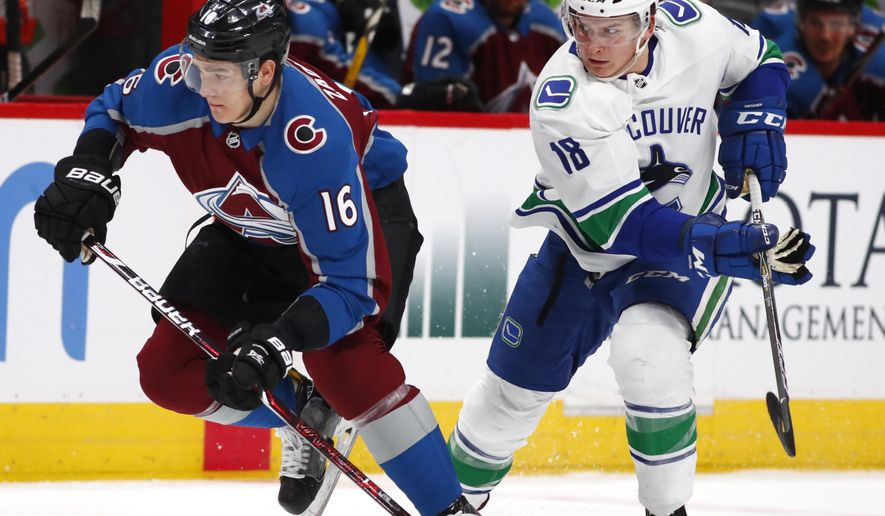 Colorado Avalanche defenseman Nikita Zadorov, left, races to pick up the loose puck with Vancouver Canucks right wing Jake Virtanen in the second period of an NHL hockey game Monday, Feb. 26, 2018, in Denver. (AP Photo/David Zalubowski)