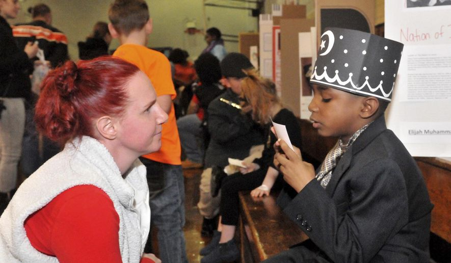 Teacher Stacey Noone listens to second grader Amir As-Salafee as he portrays Elijah Muhammad during a living wax museum at Samuel Smith Elementary School in Burlington City, N.J., Thursday, Feb. 22, 2018. The students at Samuel Smith Elementary School dressed up as famous African-Americans in honor of black history month. (Carl Kosola/Burlington County Times via AP)