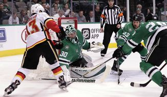 Dallas Stars goalie Ben Bishop (30) deflects a shot from Calgary Flames left wing Johnny Gaudreau (13), as Stars defensemen Marc Methot (33) and Stephen Johns (28) look to clear it during the second period of an NHL hockey game Tuesday, Feb. 27, 2018, in Dallas. (AP Photo/Tony Gutierrez)