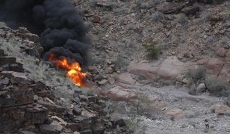 FILE - In this Saturday, Feb. 10, 2018, file photo, a survivor, lower right, walks away from the scene of a deadly tour helicopter crash along the jagged rocks of the Grand Canyon, in Arizona. The company whose helicopter was involved in the deadly crash is adding crash-resistant fuel systems to its fleet. Papillon Airways announced an agreement Monday, Feb. 26, 2018, with StandardAero for 40 fuel tanks that expand, rather than rupture, on impact. The systems also have self-sealing components. (Teddy Fujimoto via AP,File)