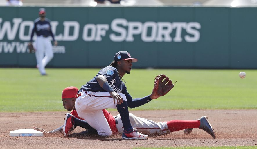 Washington Nationals' Victor Robles, back left, steals second base as he gets past Atlanta Braves second baseman Ozzie Albies during the first inning of an exhibition spring baseball game, Monday, Feb. 26, 2018, in Kissimmee, Fla. (AP Photo/John Raoux)