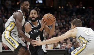 San Antonio Spurs' Patty Mills, center, from Australia, drives between Cleveland Cavaliers' Jeff Green, left, and Kyle Korver in the first half of an NBA basketball game, Sunday, Feb. 25, 2018, in Cleveland. (AP Photo/Tony Dejak)
