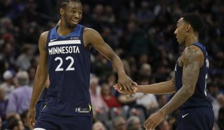 Minnesota Timberwolves forward Andrew Wiggins, left, slaps hands with teammate Jeff Teague as they leave the court during a timeout during the second half of an NBA basketball game against the Sacramento Kings, Monday, Feb. 26, 2018, in Sacramento, Calif. The Timberwolves won 118-100. (AP Photo/Rich Pedroncelli)
