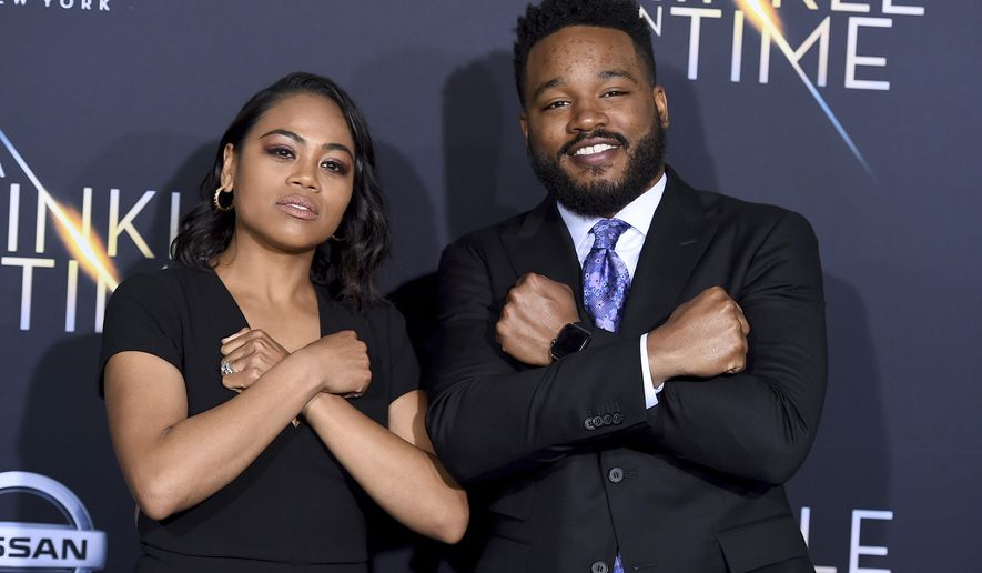 """Zinzi Evans, left, and Ryan Coogler gesture the """"Wakanda Forever"""" symbol from the film """"Black Panther"""" as they arrive at the world premiere of """"A Wrinkle in Time"""" at the El Capitan Theatre on Monday, Feb. 26, 2018, in Los Angeles. (Photo by Jordan Strauss/Invision/AP)"""