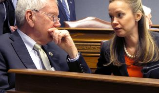 In a Sunday, Feb. 205, 2018 photo, House Health and Welfare Chairman Frank Hoffmann, R-West Monroe, speaks with Rep. Helena Moreno, D-New Orleans, during a hearing on bills that would impact Louisiana's Medicaid program, in Baton Rouge, La. (AP Photo/Melinda Deslatte)