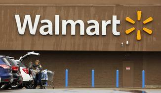 A shopper loads her car after shopping at a Walmart in Pittsburgh, Thursday, Feb. 22, 2018. (AP Photo/Gene J. Puskar)