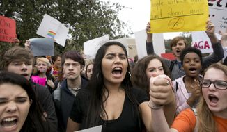 Madison Flores, 17, middle, participates in a walkout and demonstration for gun control at Anderson High School in Austin, Texas, on Friday Feb. 23, 2018. (Jay Janner/Austin American-Statesman via AP)