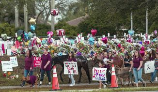 Supporters greet arriving students at Marjory Stoneman Douglas High School on Wednesday, Feb. 28, 2018 in Parkland, Fla.  With a heavy police presence, classes resumed for the first time since several students and teachers were killed by a former student on Feb. 14.   (Matias J. Ocner/Miami Herald via AP)