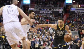 Golden State Warriors guard Stephen Curry (30) drives to the basket against Washington Wizards forward Tomas Satoransky, center, and center Marcin Gortat (13), of Poland, during the first half of an NBA basketball game Wednesday, Feb. 28, 2018, in Washington. (AP Photo/Nick Wass)