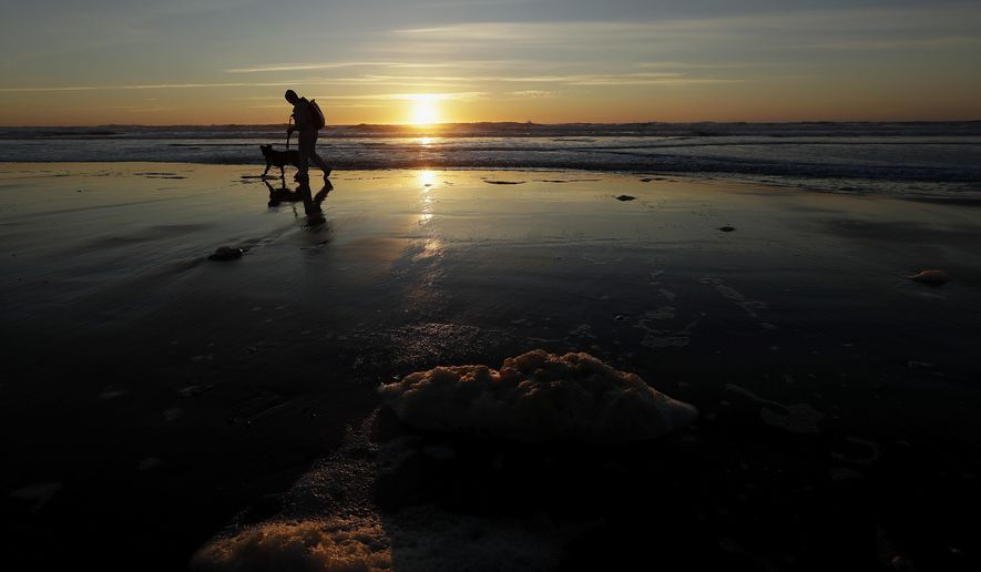 A man walks his dog at Ocean Beach as the sun sets in San Francisco, Tuesday, Feb. 27, 2018. Forecasters said the next weather system will arrive in Northern California on Wednesday, and reach the south by Thursday, bringing much more precipitation. (AP Photo/Jeff Chiu)