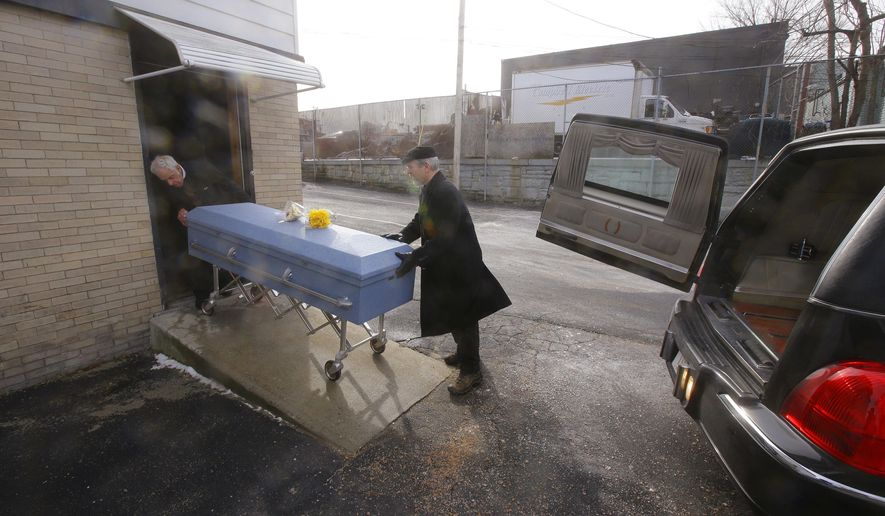 In this Thursday, Feb. 1, 2018, photo, funeral director Paul St. Germaine, left, and driver Richard Derosiers wheel a casket containing the body of 82-year-old James Oram from the Graham Putnam & Mahoney Funeral Parlor to a hearse waiting to take Oram to his final resting place in Worcester, Mass. Oram died at a local nursing home and his body was unclaimed, leading to its retrieval by funeral director and proprietor Peter Stefan, who buried Oram in an unmarked grave at Hope Cemetery in Worcester. (AP Photo/Stephan Savoia)