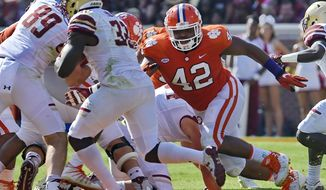 FILE - In this Sept. 23, 2017, file photo, Clemson's Christian Wilkins (42) pursues a runner during the first half of an NCAA college football game against Boston College Clemson, S.C. The secret to Clemson retaining its stellar defensive line is not that mysterious, Tigers coach Dabo Swinney says: Expected first-rounders Christian Wilkins, Clelin Ferrell and Austin Bryant did not get the grades they anticipated from the NFL committee evaluating their draft chances. (AP Photo/Richard Shiro, File)