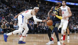Los Angeles Clippers forward Tobias Harris, left, knocks the ball away from Denver Nuggets guard Will Barton, center, who had driven by Clippers center Boban Marjanovic during the second half of an NBA basketball game Tuesday, Feb. 27, 2018, in Denver. The Clippers won 122-120. (AP Photo/David Zalubowski)