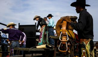 In this Sunday, Feb. 18, 2018 photo,  E.J. Wright prepares his saddle as he gets ready for a saddle bronc ride in the arena at the Branded for Christ Cowboy Church, in Huntsville, Texas. (Michael Ciaglo/Houston Chronicle via AP)