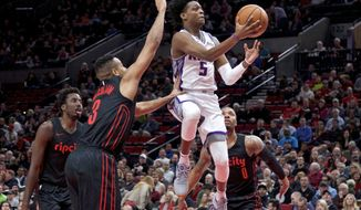 Sacramento Kings guard De'Aaron Fox, center, shoots over Portland Trail Blazers guard Damian Lillard, right, guard CJ McCollum, second from left, and forward Al-Farouq Aminu, left, during the first half of an NBA basketball game in Portland, Ore., Tuesday, Feb. 27, 2018. (AP Photo/Craig Mitchelldyer)