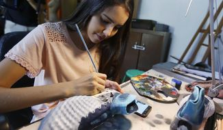In this Feb. 20, 2018 photo, Paraguayan artist Lilian Cantero paints a pair of soccer cleats in San Lorenzo, Paraguay. Cantero has received requests for her work from all over the world after Lionel Messi posed in a photograph with the cleats that she sent him as a gift. (AP Photo/Jorge Saenz)