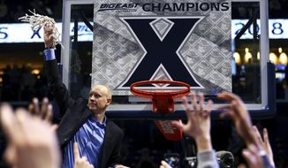 Xavier's head coach Chris Mack holds up the net after clinching at least a share of its first Big East championship after an NCAA college basketball game against Providence, Wednesday, Feb. 28, 2018, in Cincinnati. Xavier won 84-74. (AP Photo/Aaron Doster)