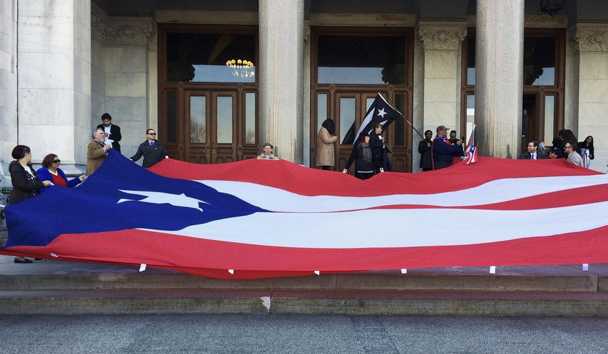 Activists hold up a flag of the U.S. territory of Puerto Rico, which was devastated by Hurricane Maria in September, during a protest outside the Connecticut state Capitol on Wednesday, Feb. 28, 2018, in Hartford, Conn. They are urging state lawmakers to support legislation that will provide financial help to the thousands who've sought refuge in the state. (AP Photo/Susan Haigh)