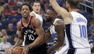 Toronto Raptors' DeMar DeRozan, left, looks to pass the ball as he is defended by Orlando Magic's Jonathon Simmons, center, and Evan Fournier (10) during the first half of an NBA basketball game Wednesday, Feb. 28, 2018, in Orlando, Fla. (AP Photo/John Raoux)