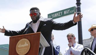 FILE - In this June 22, 2017, file photo, retired Boston Red Sox designated hitter David Ortiz is honored with the renaming of a portion of Yawkey Way to David Ortiz Drive outside Fenway Park in Boston. Beside him are Boston Mayor Marty Walsh, second from right, and team owner John Henry, right. In February 2018, the Red Sox asked the city of Boston to change the name of the rest of Yawkey Way back to its original Jersey Street name. The street had been named for late Sox owner Tom Yawkey, who owned the team from 1933 to 1976 and presided over the last franchise in Major League Baseball to field a black player. That was in 1959, more than a decade after Jackie Robinson played for the Dodgers. (AP Photo/Charles Krupa, File)