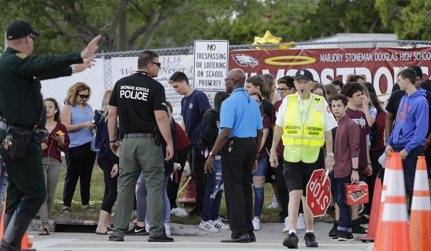 Students wait to cross the street after their first day back at Marjory Stoneman Douglas High School in Parkland, Fla., Wednesday, Feb. 28, 2018.  The students were greeted Wednesday morning by police officers carrying military style rifles and an array of counselors and therapy dogs. They missed two weeks of school following the Feb. 14 mass shooting that killed several students and teachers.  (AP Photo/Terry Renna)
