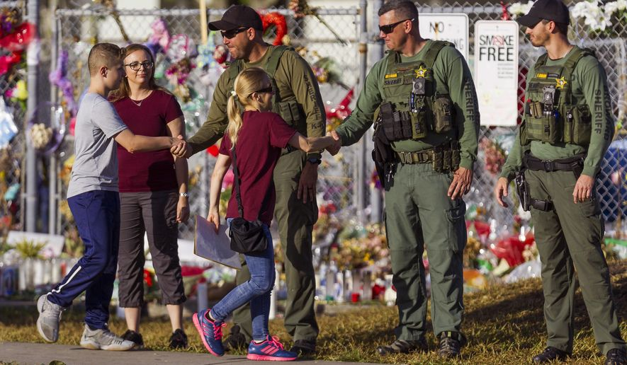 Faculty and staff greet police officers stationed outside of at Marjory Stoneman Douglas High School on Wednesday, Feb. 28, 2018 in Parkland, Fla.  With a heavy police presence, classes resumed for the first time since several students and teachers were killed by a former student on Feb. 14.   (Matias J. Ocner/Miami Herald via AP)