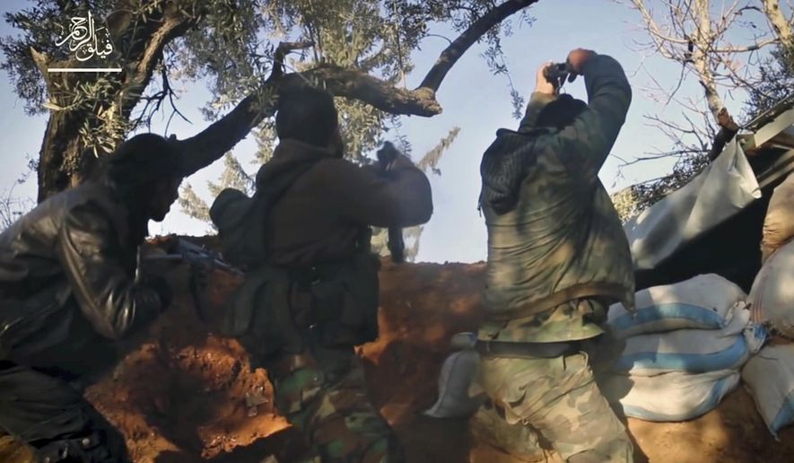 This frame grab from video provided Nov. 24, 2017, by the Syrian insurgent group Failaq al-Rahman, shows fighters with Failaq al-Rahman firing their weapons during clashes with government forces in the suburbs of the Syrian capital Damascus. Many of the fighters entrenched in the Damascus suburb of eastern Ghouta are originally from the area and move around using an elaborate network of underground tunnels, giving them an advantage against President Bashar Assad's forces and their allies. (Failaq al-Rahman, via AP)