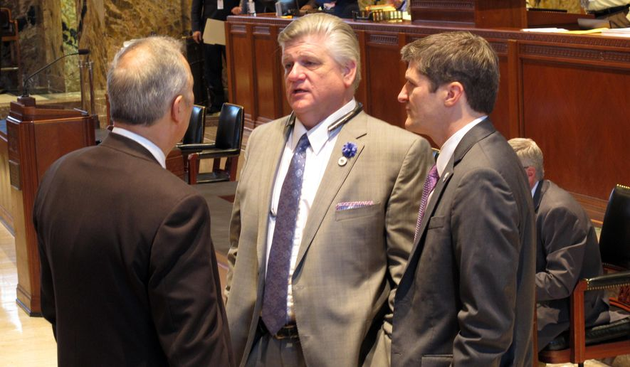 House Republican leader Lance Harris, center, speaks with Rep. Mark Abraham, R-Lake Charles, left, and Patrick Goldsmith, director of the House Fiscal Division, on the House floor on Wednesday, Feb. 28, 2018, in Baton Rouge, La. (AP Photo/Melinda Deslatte)